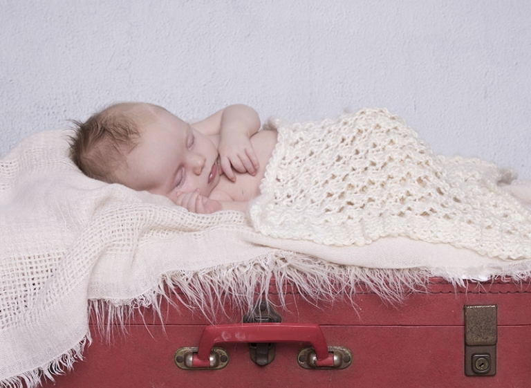 newborn on a red vintage suitcase