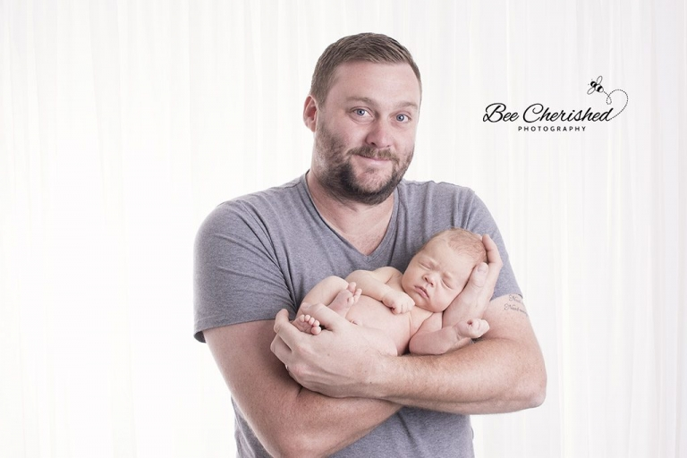 proud father holding a newborn baby