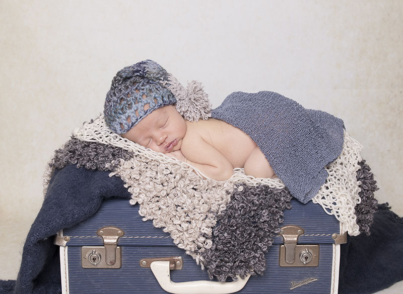 old navy suitcase with a newborn boy on top wearing a cute sleepy hat